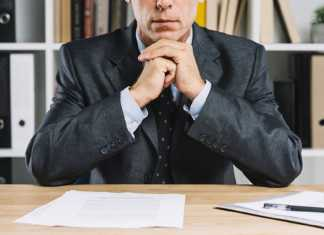 A man with papers on his desk, thinking about how to deal with his challennges